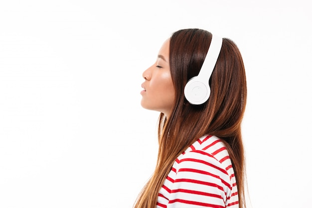 Side view of a young asian girl in headphones