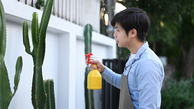 Side view of young asian man using a water bottle to watering cactus at his garden.