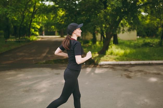側面図黒のユニフォームとキャップトレーニング、スポーツエクササイズとランニング、屋外の都市公園の小道をまっすぐ見ている若い運動ブルネットの女の子