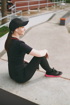 Side view young athletic brunette woman in black uniform and cap with headphones listening to music resting and sitting before or after running, training in city park outdoors