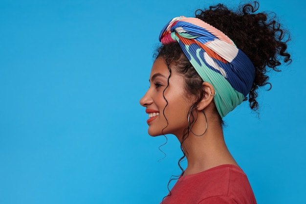 Side view of young attractive brunette woman with gathered curly hair looking cheerfully ahead with broad sincere smile while standing over blue wall