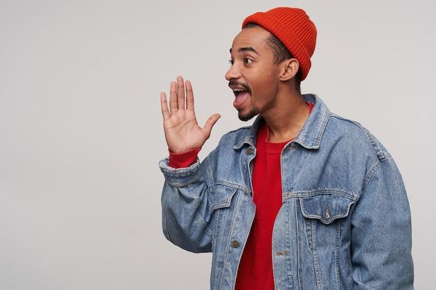 Vista laterale del giovane hipster brunetta dalla pelle scura con la barba che guarda da parte e urla qualcosa, alzando il palmo alla bocca mentre posa su bianco