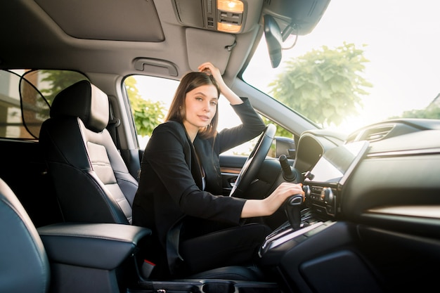 Side view of young beautiful business woman sitting in her car on driver seat  sunny day. business woman in car