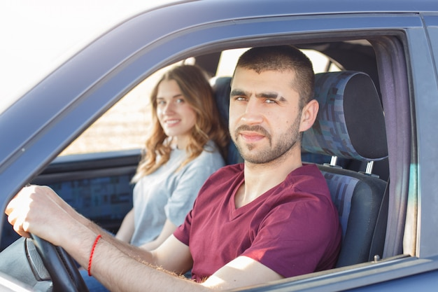 Side view of young beautiful couple has trip in car