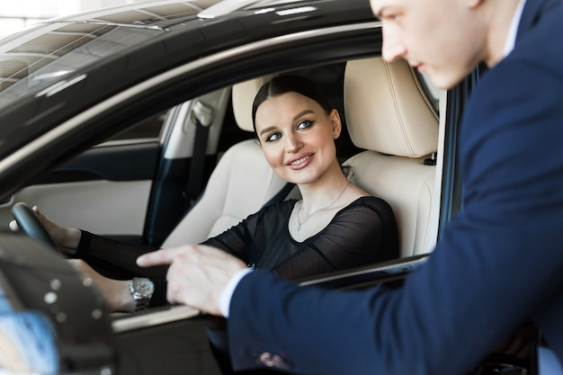 Side view of young beautiful woman sitting inside car and holding hand on steering wheel. she smiling and talking with manager of car dealership. car agent representing inside of automobile.
