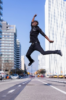 Side view young black man wearing casual clothes jumping in street