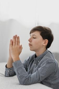 Giovane ragazzo di vista laterale che prega pacificamente