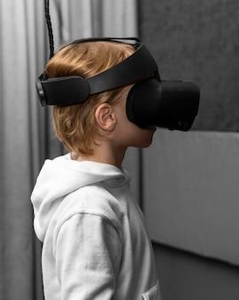 Vista laterale del giovane ragazzo utilizzando le cuffie da realtà virtuale