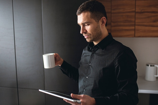 Side view of young businessman in kitchen work remote. entrepreneur hold tablet and look at it. drink tea during coffee break. efficient work at home. company ceo.