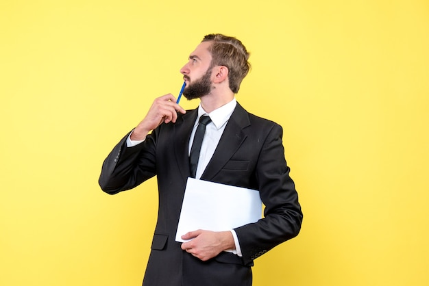 Side view of young businessman looks aside putting pencil on mouth and thinking or having an idea on the yellow wall