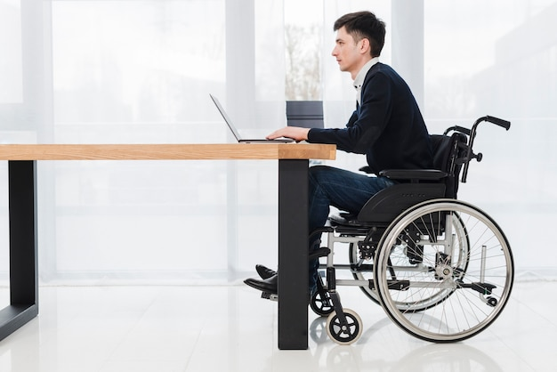 Side view of a young businessman sitting on wheelchair using laptop in new office
