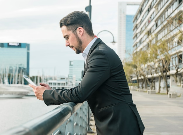 Side view of a young businessman standing near the railing using smartphone