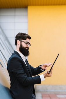 Side view of a young businessman using digital tablet standing against wall