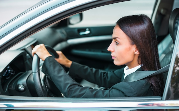 Side view of a young businesswoman driving car
