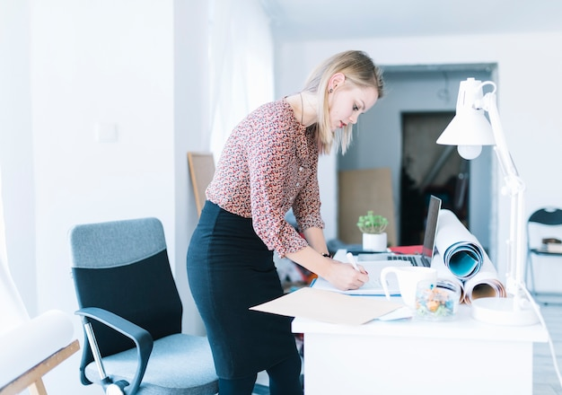 Side view of a young businesswoman standing near desk writing in office