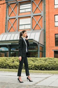 Side view of a young businesswoman talking on cell phone standing in front of building