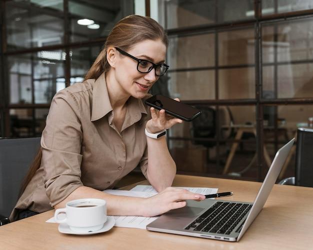 Vista laterale della giovane imprenditrice parlando al telefono durante una riunione