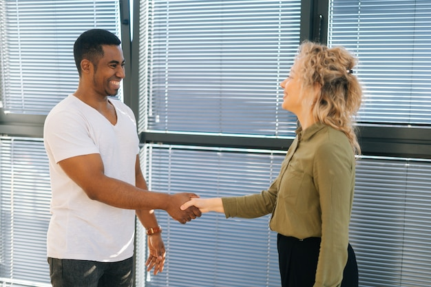 Side view of young caucasian businesswoman having conversation with african american male colleague near window. handshake of businessmen people at business conference after successful negotiation.