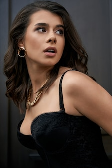 Side view of young caucasian stunning woman wearing black lace corset and golden accessories looking aside. closeup portrait of female model posing near wooden door outdoors.