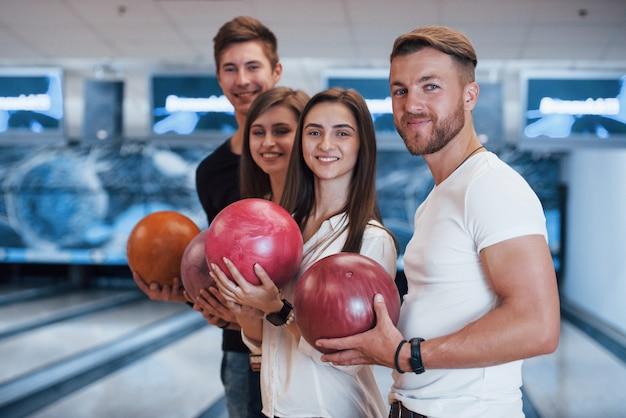 Vista laterale. i giovani amici allegri si divertono al bowling durante i fine settimana