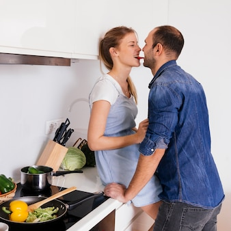 Side view of a young couple eating the carrot together in the kitchen