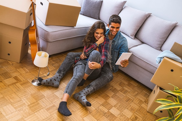 Side view of young couple sitting on floor near carton boxes and browsing modern laptop while moving into new apartment together