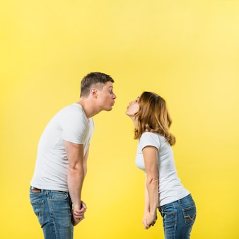 Side view of a young couple standing face to face blowing kisses against yellow background