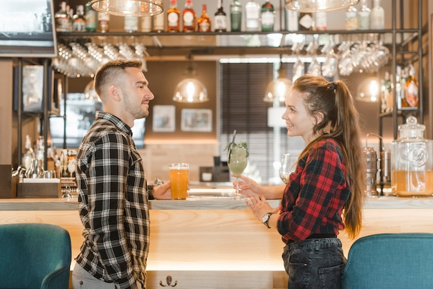 Side view of young couple standing near the bar counter looking at each other