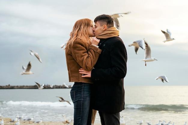 Vista laterale della giovane coppia in inverno sulla spiaggia