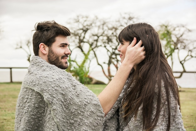 Side view of young couple wrapped in the blanket