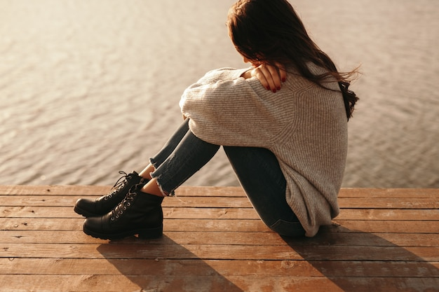 Side view of young depressed female embracing knees while sitting on wooden quay near water alone