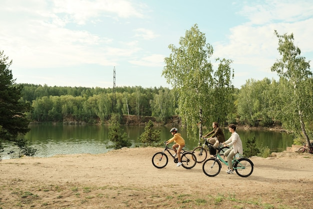 Side view of young family sitting on bicycles and moving along riverbank on green trees while enjoying active rest together