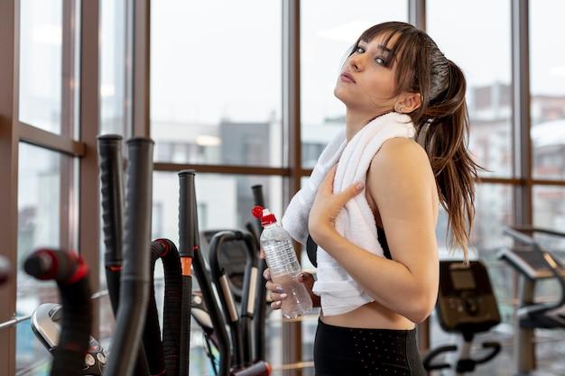 Вид сбоку молодая женщина в тренажерном зале