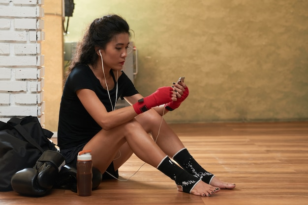 Side view of young female athlete listening to music after the workout