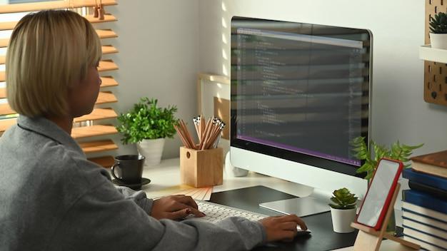 측면 보기 젊은 여성 프로그래머가 사무실에서 새 프로젝트를 진행하고 있습니다.