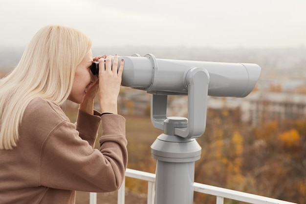 Side view of young female tourist with blond hair in casual clothes sightseeing city with telescope binoculars standing on observation deck on autumn day