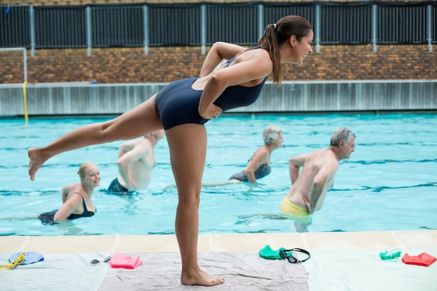 Side view of young female trainer assisting senior swimmers