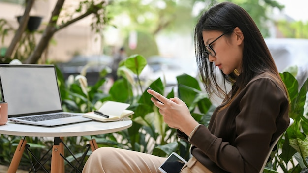 Side view of young female worker using smartphone while relaxed sitting in garden at office
