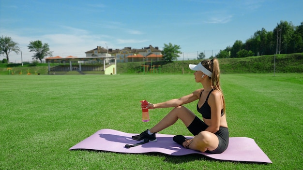Side view of young fit woman holding bottle with water, sitting on mat, stadium field in summer sunny day. athletic girl wearing sports outfit having rest on green grass. concept of sport, workout.