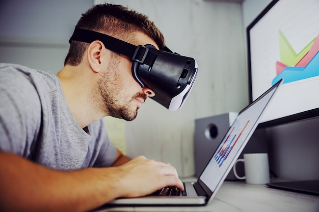 Side view of young freelancer using vr technology while working on analysis for monthly salary on stock market. on displays are charts. home office interior.