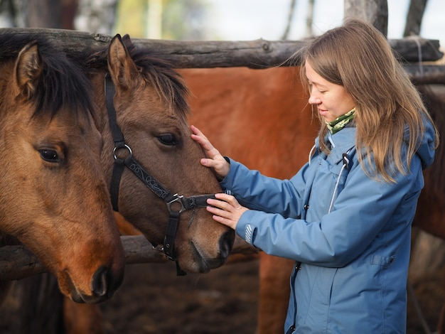 Side view of a young girl touching the horses Premium Photo