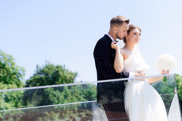 Side view of young groom hugs his bride, standing on the terrace of a summer day