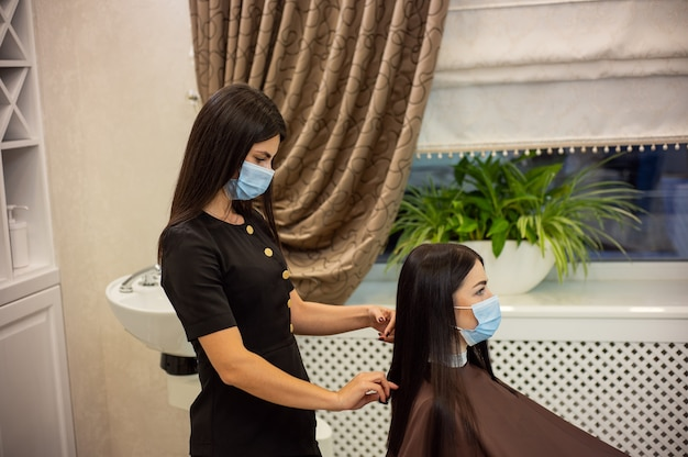 Side view of young hairdresser and customer in beauty salon during pandemic