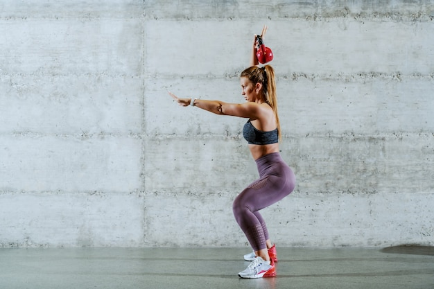 Side view of young handsome dedicated caucasian sportswoman with ponytail standing in squat position and lifting kettle bell.