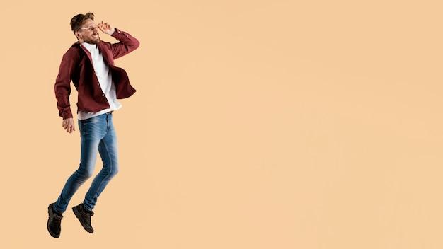 Giovane uomo bello di vista laterale che salta