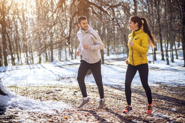 Side view of young happy charming smiling fitness sporty couple in winter sportswear jogging in the snowy forest.