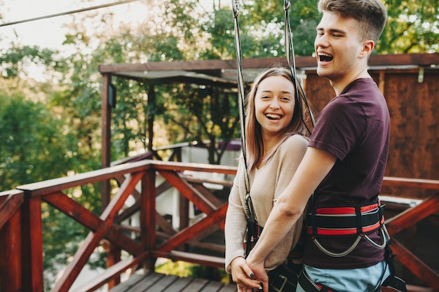 Side view of young happy couple in special gear with safety harness hanging on cable for zip line ride in park
