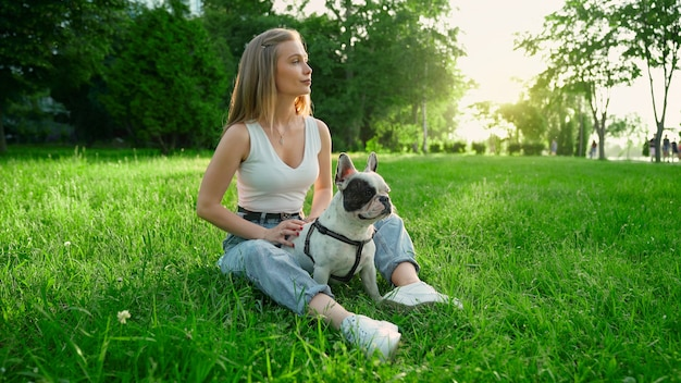 Side view of young happy woman sitting on fresh grass with cute white and brown french bulldog. gorgeous smiling girl enjoying summer sunset, petting dog in city park. human and animal friendship.