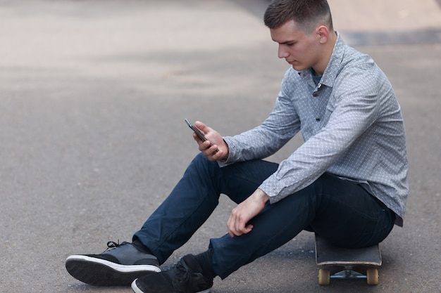 Side view - young hipster guy sits on skateboard on the road and typing on the smartphone during break in the park on warm summer day