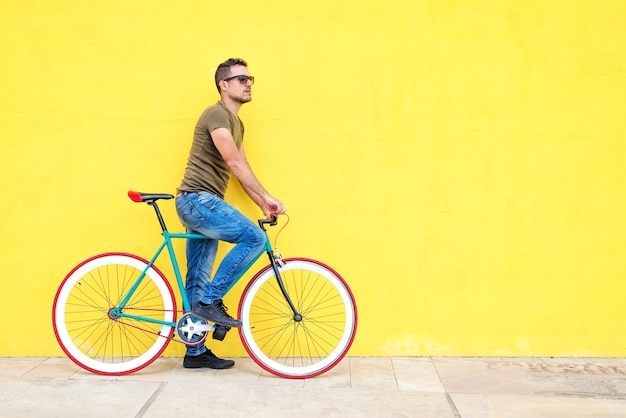 Side view of a young hipster man with a fixed bike wearing casual clothes